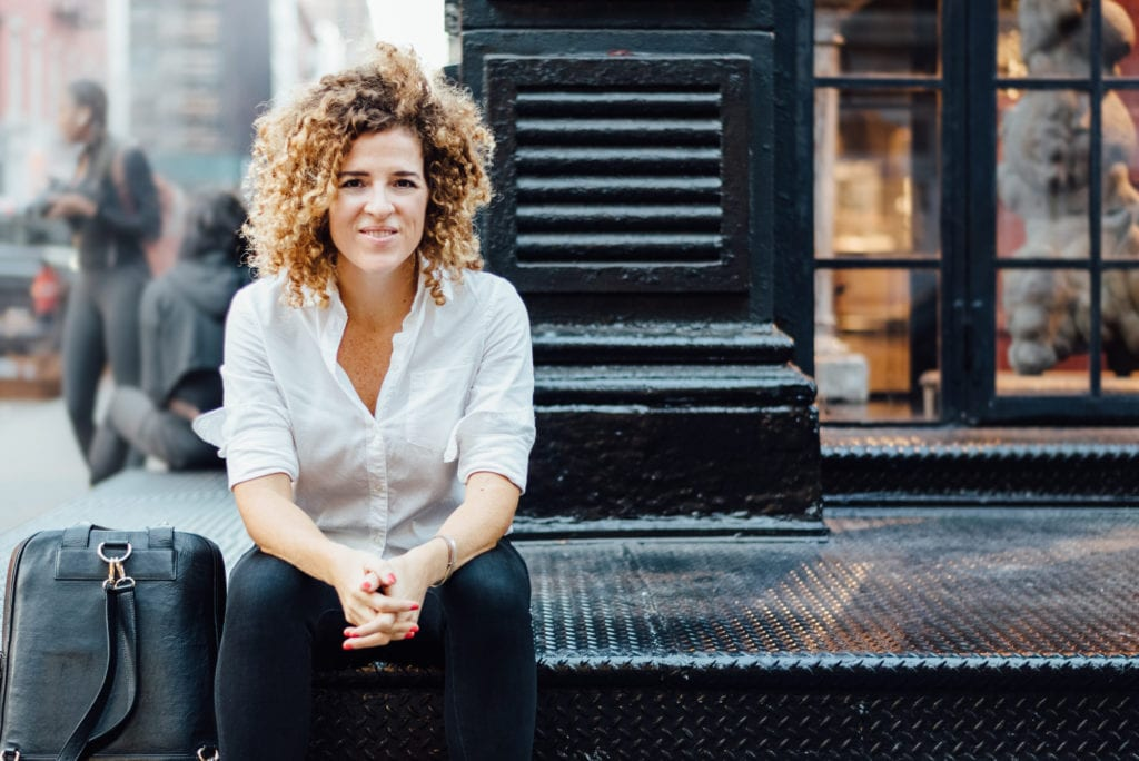 Sarah Doody sitting on a stoop of a building in New York City.