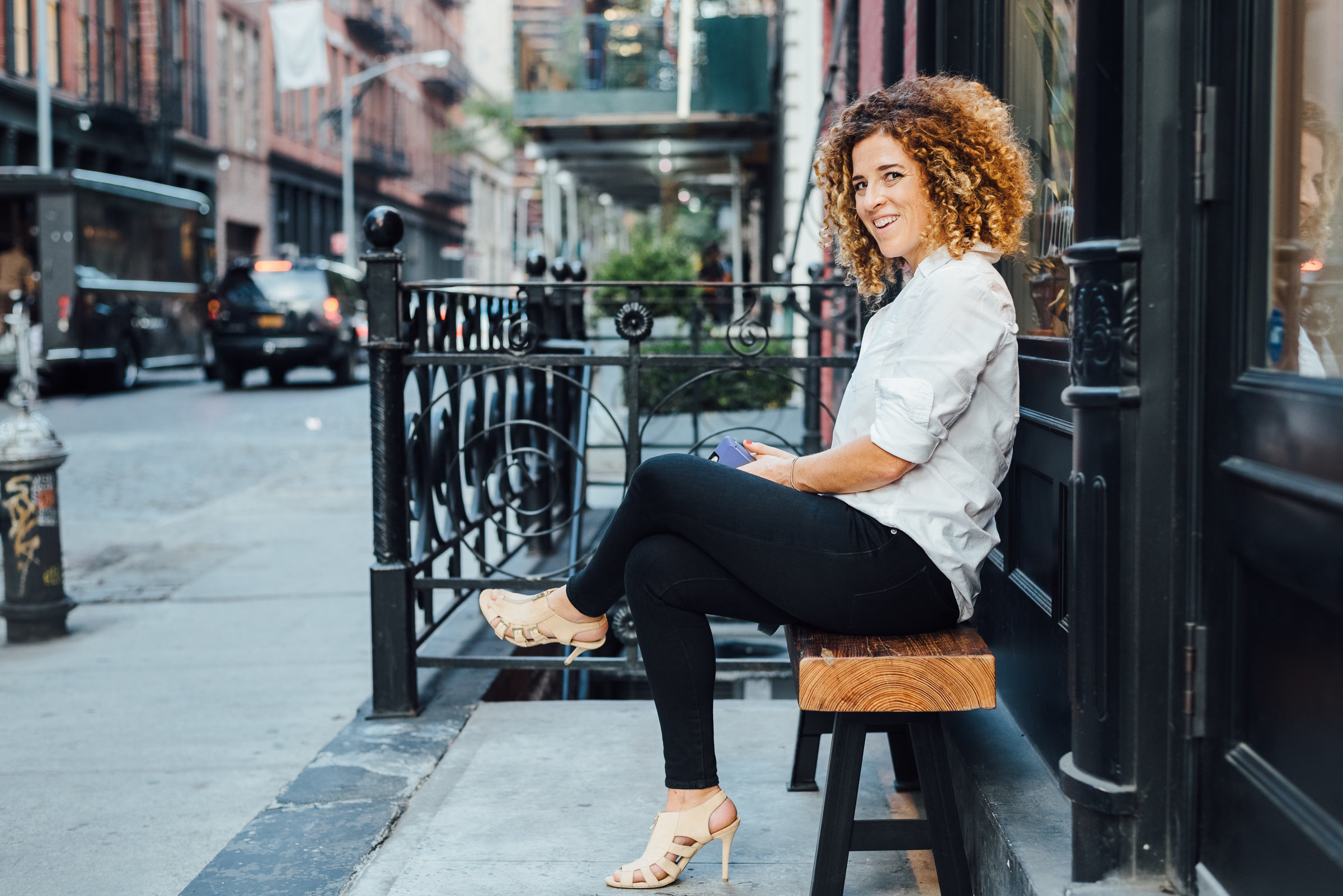Sarah Doody, UX Portfolio Founder, sitting on a bench in New York City.